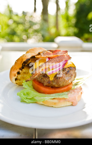 An American classic bacon cheeseburger fresh from the grill sits on a plate - Stock Photo