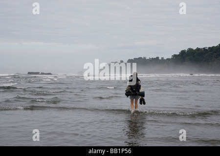 A hiker crosses a river along the coast in Corcovado National Park, Costa Rica. - Stock Photo