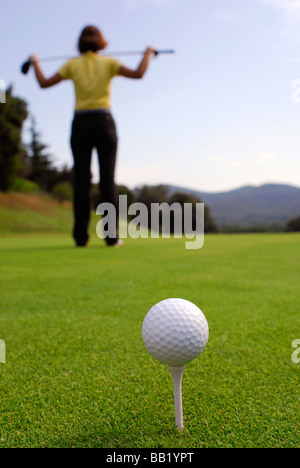 Young woman golfer observing terrain and conditions before hitting - Stock Photo