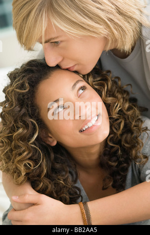 Teenage boy kissing on the forehead of a girl - Stock Photo