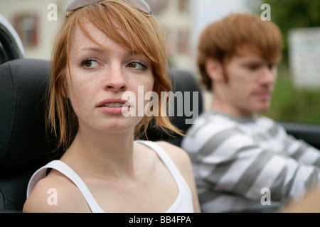 Portrait of of young couple in a car - Stock Photo