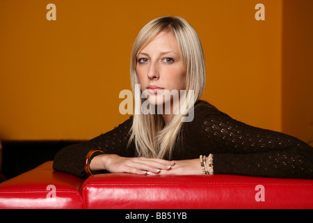 Portrait of young woman in a lounge - Stock Photo