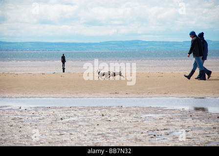 Couple walking their dog on Crosby beach. With one of Antony Gormley's Another Place art figures in the background. - Stock Photo