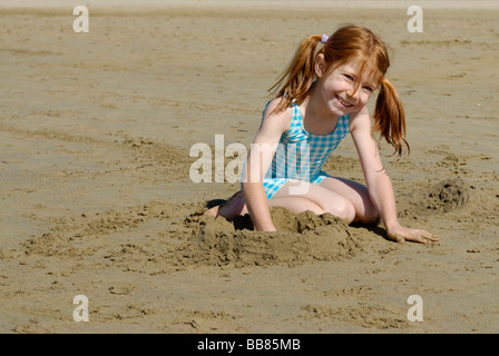 Girl lying and playing on the beach, seaside of the Adria, Bibione, Venetia, Venice, Italy, Europe - Stockfoto