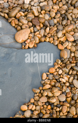 Sea washed pebbles surrounding a limestone rock on the beach at Charmouth - Stock Photo