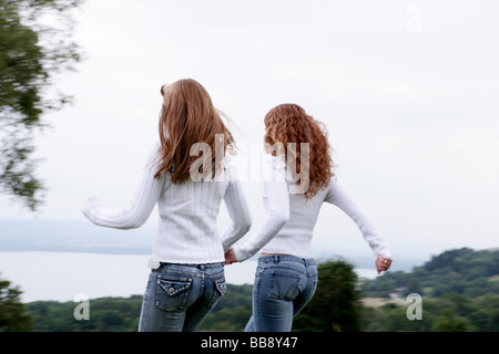 Two teenagers walking on a field with lake view - Stock Photo