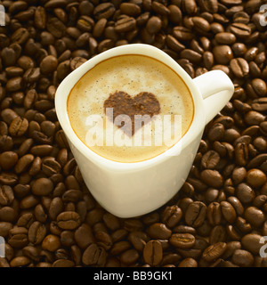 A cup of coffee cappuccino style with a heart shape on the top, shot on coffee beans. - Stock Photo