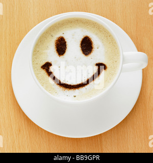 A cup of coffee cappuccino style with a smiley face on the top in chocolate powder, shot on a table top. - Stock Photo