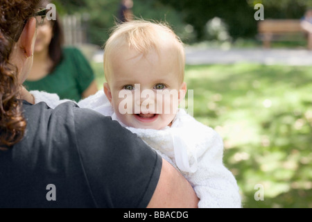 A mother carrying her baby girl, over the shoulder view - Stock Photo