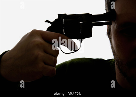 Detail of a man holding a gun to his head - Stock Photo