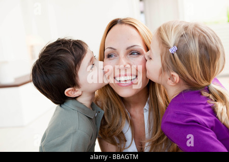 brother and sister kissing her mother - Stock Photo