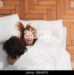 Couple fooling around in bed - Stock Photo