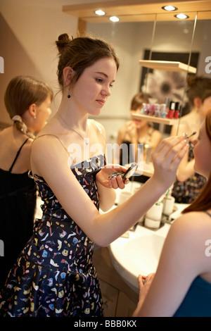 Teenage girls applying make-up - Stock Photo