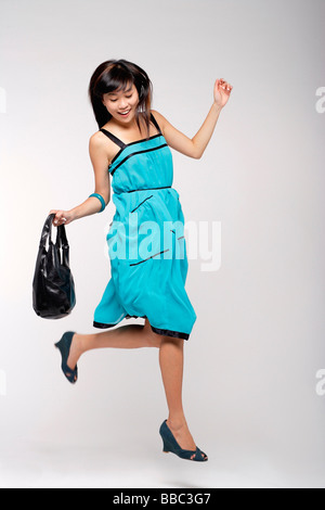 Young woman wearing blue dress, holding purse and jumping - Stock Photo