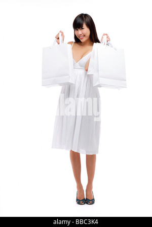Young woman wearing white dress and holding white shopping bags, smiling - Stock Photo