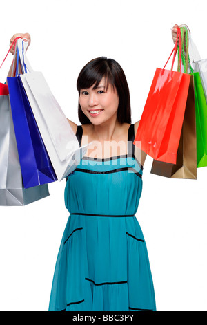 Young woman wearing blue dress and holding shopping bags up in air - Stock Photo