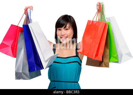 Young woman wearing blue dress and holding colorful shopping bags up in air - Stock Photo