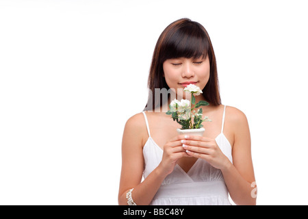 Young woman wearing white dress, holding small plant and smelling flower - Stock Photo