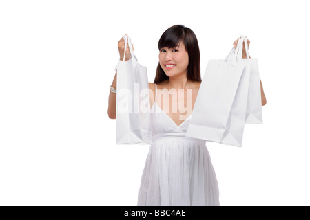 Young woman wearing white dress and holding white shopping bags up in air - Stock Photo