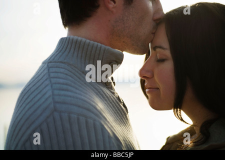 Man kissing woman's forehead at sunset - Stock Photo