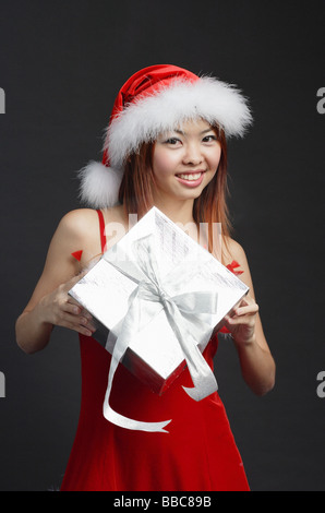 Woman wearing Santa hat and red dress, holding silver gift box - Stock Photo