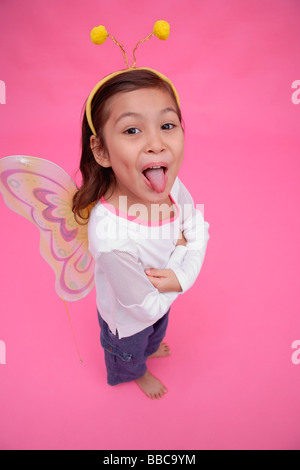 Young girl wearing fairy wings and deely bopper, arms crossed, sticking out tongue - Stock Photo