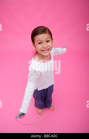 Girl with skipping rope, smiling up at camera - Stockfoto