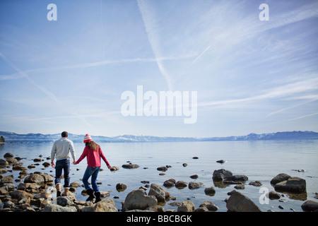Couple walking on rocks near lake - Stock Photo
