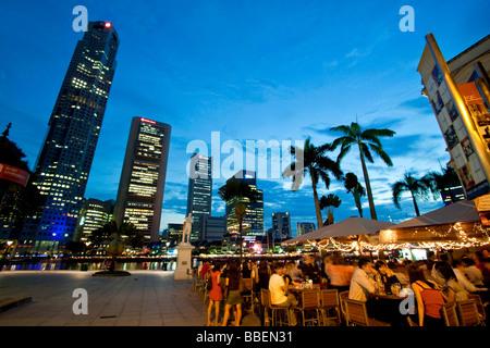 Skyline of Singapores Raffles Statue street cafe South East Asia twilight - Stock Photo