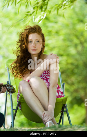 Young woman sitting in folding chair outdoors, looking away - Stock Photo