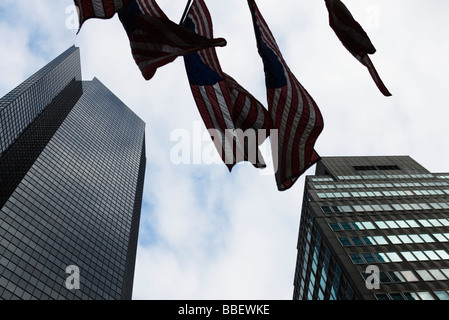 Skyscrapers, flags waiving in breeze, viewed from below - Stock Photo