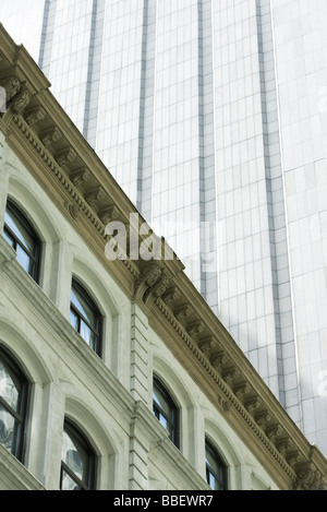 Facade of neoclassical building, modern skyscraper towering above, low angle view - Stock Photo
