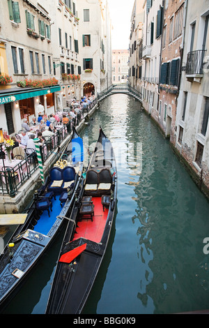 A restaurant and gondolas on a canal in venice - Stock Photo