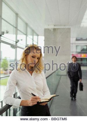 Businesswoman writing personal organizer - Stock Photo