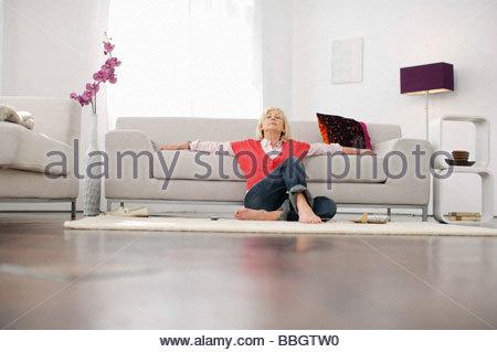 Senior woman relaxing living room - Stock Photo