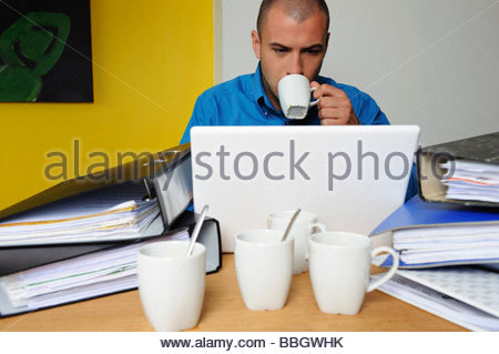 Portrait young man sitting at desk drinking coffee - Stock Photo