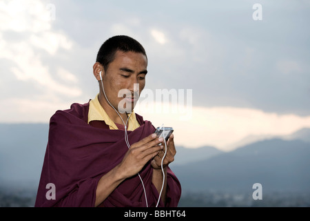 Pokhara, Nepal; Monk listening to i-Pod - Stock Photo