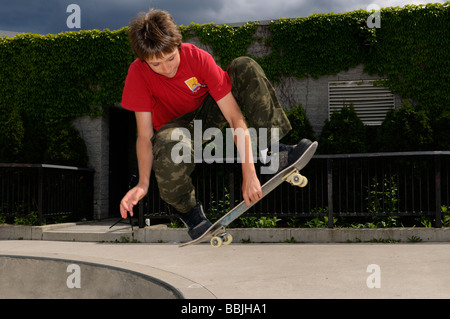 Airborne boy doing a mute grab Slobair on a skateboard above a concrete bowl at a Toronto outdoor Park - Stock Photo