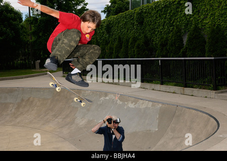 Young boy airborne on a skateboard above a concrete bowl at an outdoor Toronto Park with photographer - Stock Photo