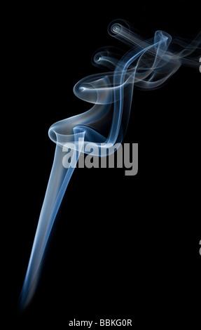 Curls of smoke given off by the slow-burning of an incense stick.Volutes de fumée dégagées par la combustion d'un - Stock Photo