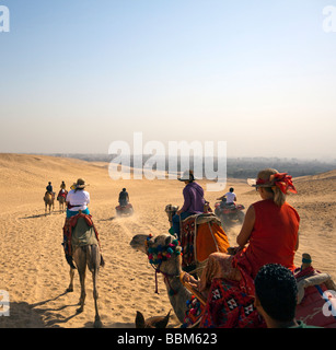 tourists riding camels and atvs (dune buggy) on sand near the Pyradmids, Giza, Cairo, Egypt - Stock Photo