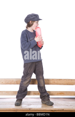 Boy wearing a cap and holding a red balloon - Stock Photo