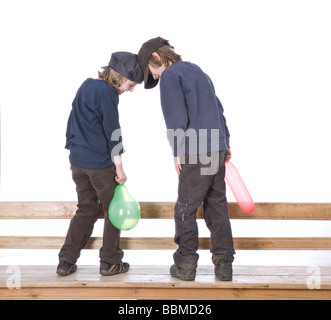 Two boys wearing caps, playing with balloons - Stock Photo