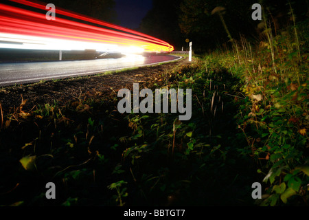 Roadside with light streaks from cars - Stock Photo