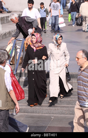 Istanbul Turkey Turkish women wearing Muslim headscarf and clothing among the crowds at Eminonu - Stock Photo