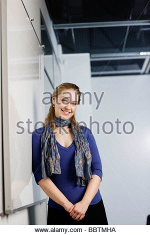 Woman smiling,  against a white board - Stock Photo