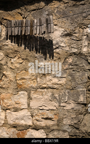 Wooden clothes pegs on washing line against stone wall - Stock Photo