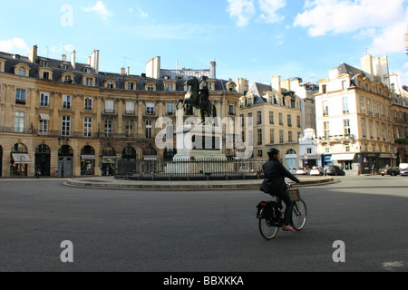 Cyclist enjoying freedom of Paris passing through Place des Victoires, Paris in front of equestrian statue of Louis - Stock Photo