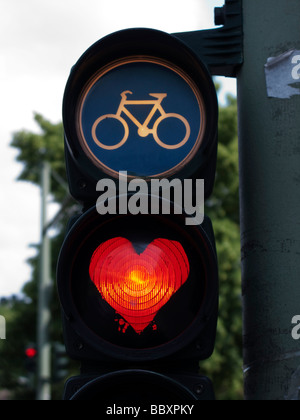 Traffic lights for cyclists with red light painted into a heart shape in Berlin Germany - Stock Photo