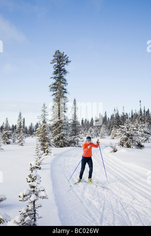 A young woman cross-country skiing. - Stock Photo
